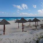 Praia do hotel com cadeiras e quiosques