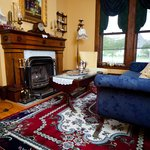 Guest Parlor w/antique sofa & chairs. Cozy up & enjoy treats with your coffee/tea near the fire.