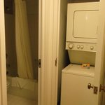Washer and dryer in cupboard next to bathroom