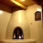 Kiva fireplace and beamed ceiling in living room
