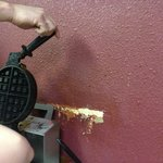 The damaged wall with peeling paint by the waffle iron