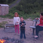 Big sister shows little brother how to roast marshmallows.