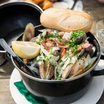 A pot of mussels with a garlic, cream, bacon and parmesan sauce. Amazing!