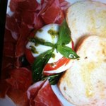 this is a delicious  dish of a caprese salad with Parma ham served with bread topped with olive