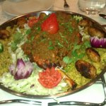 Leg of lamb covered in mince meat on a bed of vegetable rice with salad and Indian sauce seperat