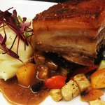 Braised pork belly with mashed potato, honey roast root vegetables, and mustard jus
