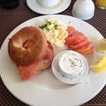 One of the breakfast choices, smoked salmon bagel with cream cheese, scrambled eggs and tomatoes