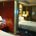 standard room. behind the privacy panel is a glass bathroom wall