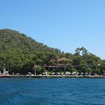 The hotel, from the water taxi to Marmaris. Hotel is behind trees in the centre, beach to the ri