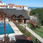 Una vista desde la habitación en la cual se puede ver todo el parque con la piscina y el mar