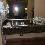 El labavo fuera dl baño tiene tiene cafetera y secadora.