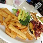 Cheese burger with lots of bacon, avocado and fries