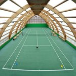 Indoor all-weather tennis court with hard coating on the roll mitigation