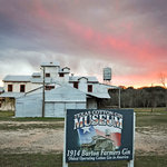The Cotton Gin in Burton, Texas with storm clouds at sunset.