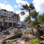 Offene Abrissruine neben dem Strand mit offenen Stromkabeln und Eisenstangen im Boden.