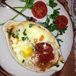 egg dish with tomatoes and topped with cheese . Served piping hot