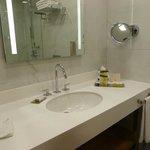 Salle de bain avec produits de toilette dont après-shampoing