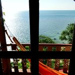 View Through Window of Villa 6 with Relaxing Hammock on Balcony for Sunset Viewing