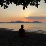 Meditierend beim Sonnenuntergang direkt am Strand vor dem Hotel