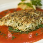 Herb crusted cod on wilted rocket with a Privencal sauce
