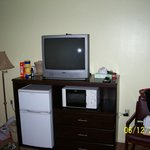 View of the tv, microwave and refrigerator