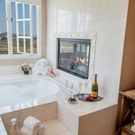 The Grand View Suite Bath with oversized jacuzzi tub, fireplace and view of the Nature Preserve