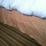 Dust ruffle on bed...lazy housekeeper evidently