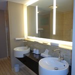 Dual sinks with nice lighting and a tv inside the mirror!