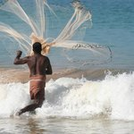 A fisherman casting his net out to sea from our beach