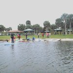 Novice paddlers getting their instruction, while others pick out and hop on their paddleboards.