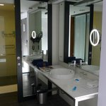 Open washbasin area with closed toilet and bath area