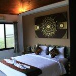 Une superbe chambre avec vue la baie, la forêt de palmiers, et la piscine de la villa