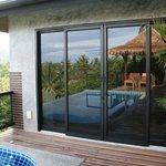 Reflet de la piscine sur la baie vitrée de la chambre