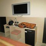 Grande televisore a parete e, sotto, l'unico arredo della camera