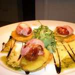 Dates wrapped in bacon on courgette fritters with rocket oil and hot honey and mustard dressing