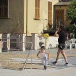 Kids playing football on the town plaza