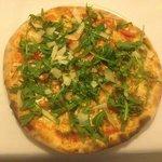 Pizza mit frischen Tomaten, Mozarella, Rucola und Parmesanscheiben