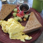 Scrambled eggs, toast and fresh fruit