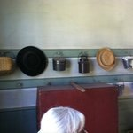 Hats and lunch pails hang on wall of school house