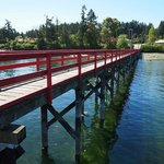 The Fernwood Dock is painted red and is situation in front of the tree lined Walker's Hook Road.