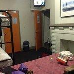 From the bed looking towards the door (bathroom door open under TV)