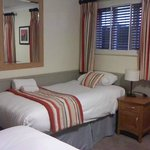One of the single beds, situated diagonally to the double bed.