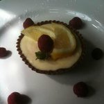 lemon posset in a chocolate shell with raspberries