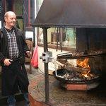 Der Wirt beim Zubereiten des Spießbratens auf offener Flamme