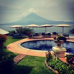 Pool deck with view of volcano and lake.