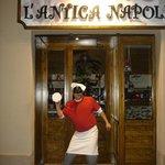 El pizzero jefe nos recibe a la entrada de la pizzería...