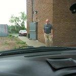 Barefoot guy hanging outside open security door