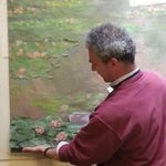 Artist holding a piece of the Waterlilies against the model painting