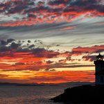 Park volunteer Stacey Kerr takes a break to snap a spectacular Lime Kiln Point Lighthouse sunset