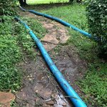 Water pipes running up muddy main path to Budget Room